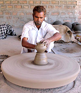 Indian modern age potter using wheel for making pottery items